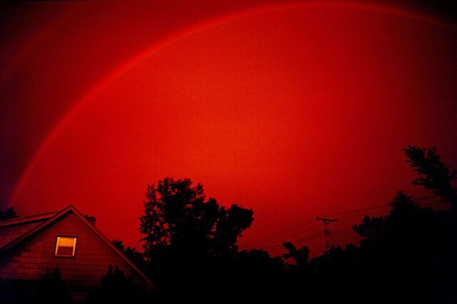Red rainbows (and sometimes even monochrome rainbows) are possible when the colours with shorter wavelengths like blue and green are scattered and thereby removed from the spectrum.